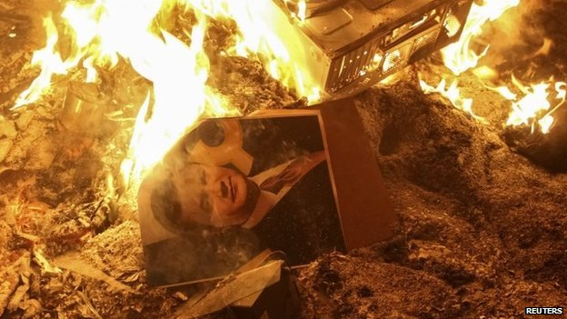 A portrait of Ukrainian President Viktor Yanukovych burns near the destroyed building of the security service in Lviv on Wednesday