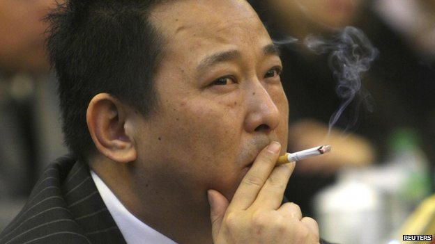 File photo: Liu Han, former chairman of Hanlong Mining, smokes a cigarette during a conference in Mianyang, Sichuan province, 21 March 2008