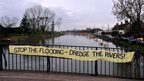 A protest banner on a bridge over the River Parrett in Burrowbridge calling for dredging to take place