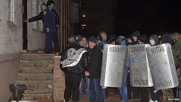 Protesters stand outside a riot police base in the town of Rivne in western Ukraine on 19 February.