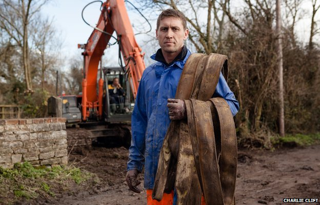A pump engineer lays a new pipeline to drain floodwater threatening dry homes