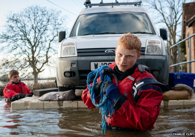Volunteers Aaron and Jay transport a trapped Environment Agency van over the flood waters on a floating pontoon
