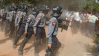 People throw bottles at Burmese riot policemen during a training session