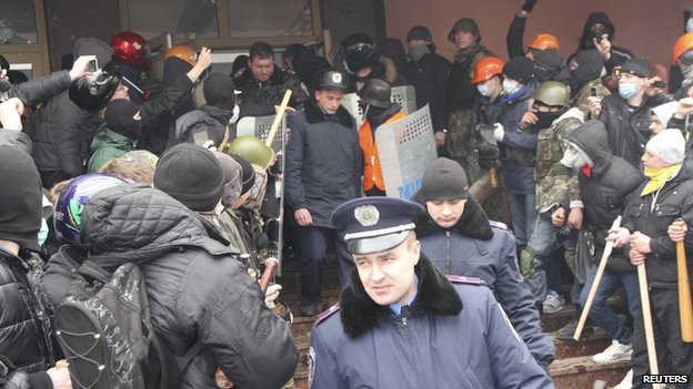 Interior Ministry members leave the building as anti-government protesters hold a rally outside an office of the Interior Ministry in the town of Lutsk in north-western Ukraine on 19 February  2014.