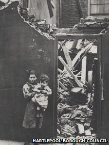 A young girl holds her toddler sibling in front of a destroyed house