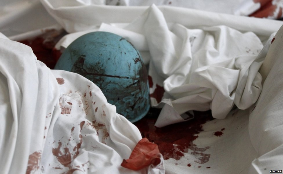 Blood-soaked helmet of an anti-government protester on a sheet in a hotel lobby in Kiev (20 February 2014)
