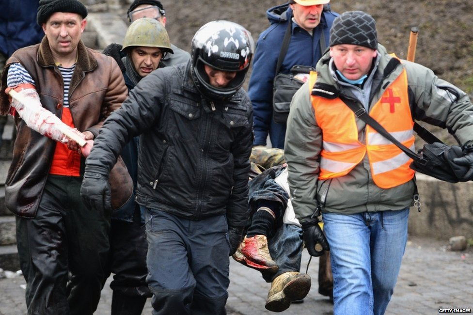 Medics and anti-government protesters carry an injured man in Kiev (20 February 2014)