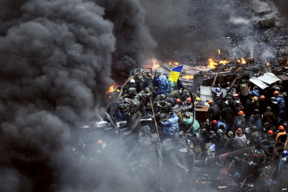Smoke billows as protesters stand behind barricades in Kiev (20 February 2014)