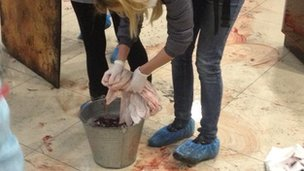 Women rinses bloody cloth in bucket of water in Hotel Ukraine on 20 February 2014