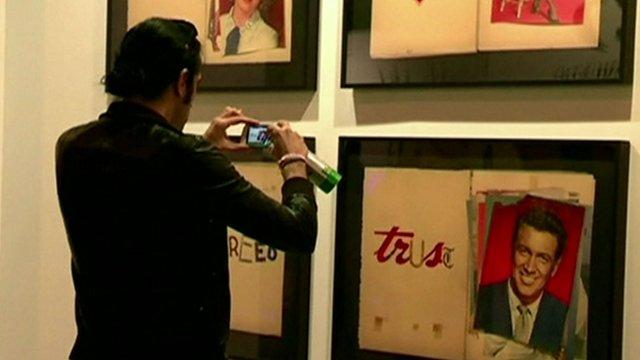 A young man takes a photograph of an artwork at the fair