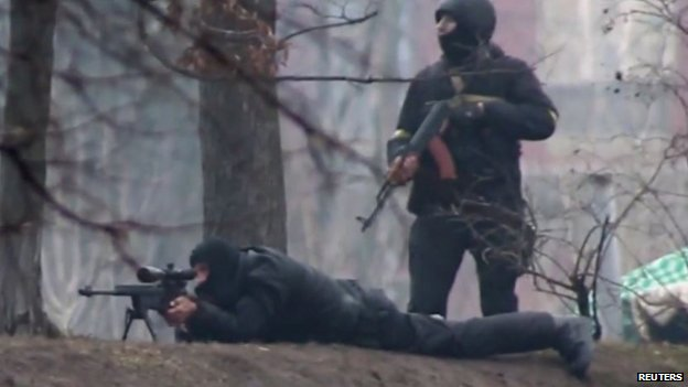 Video still provided by Radio Free Europe/Radio Liberty shows a riot police standing next to a sniper firing from a fortified position in the direction of protesters in Kiev (20 February 2014)