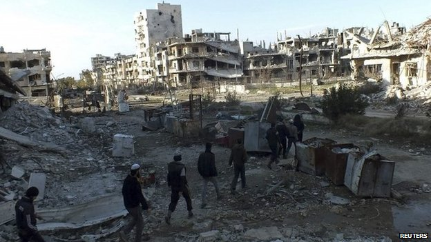 Residents walk among debris in besieged area of Homs on 14 February 2014
