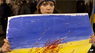 A woman holds a Ukrainian flag with red paint to represent blood, in front of the Ukrainian embassy in Warsaw, Poland, on 20 February 2014.