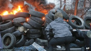 An activist looks for a sniper through a burning tire barricade close to Independence Square, the epicentre of the country's current unrest, in Kiev, Ukraine, on 20 February 2014.