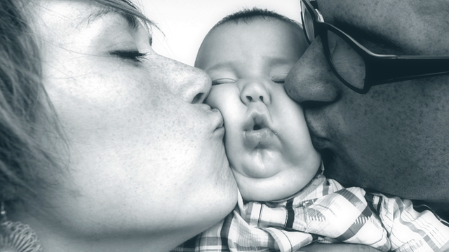 Mother and father kissing baby on both cheeks