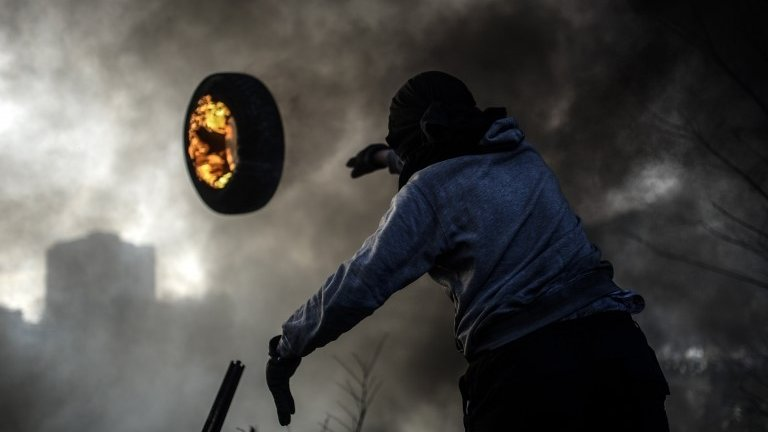 An anti-government demonstrator throws a burning tire as he build a barricade _n February 21