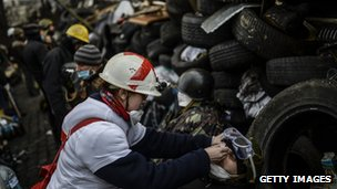 An anti-government protestor receives a medical assistance behind a barricade in Kiev, Ukraine.