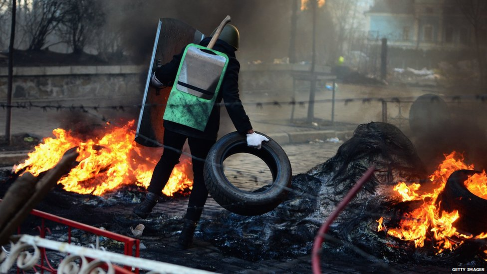 A protester adds a car tyre to fire barricades