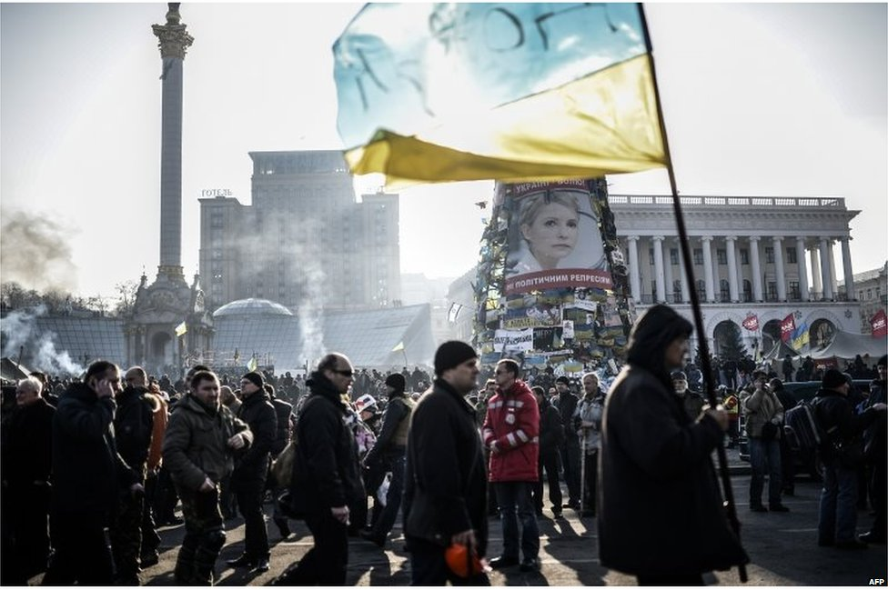 Protesters in Independence square, with a large poster of Ukrainian opposition leader and former Prime Minister Yulia Tymoshenko in the background