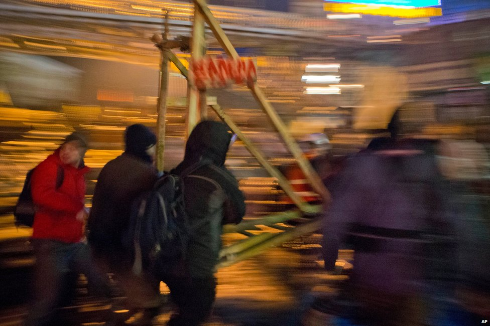 Protesters carry a catapult - used to hurl petrol bombs and missiles at police - to the front line, overnight