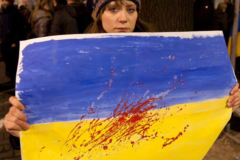 A woman holds an Ukrainian flag with red paint spattered on it to represent blood, in front of the Ukrainian embassy in Warsaw, Poland (21 February 2014)