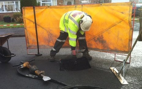 Worker fixing pothole
