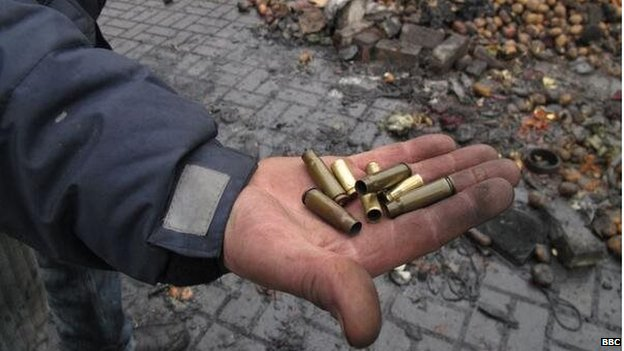 A protester holds up spent bullets allegedly fired by security forces