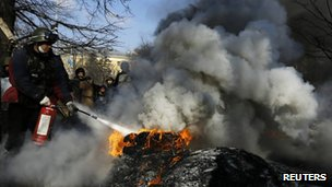 Man puts out burning tyres in Kiev, Ukraine