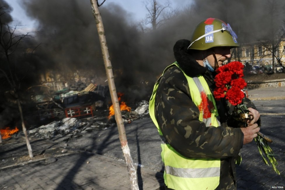 Anti-government protester carries flowers in Kiev (21 February 2014)
