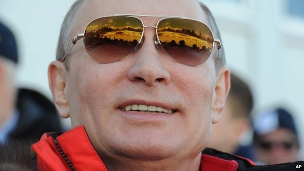 Russian President Vladimir Putin smiles as he watches the 4x10km cross-country relay at the 2014 Winter Olympics, Feb 16
