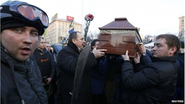 People carry the coffin of an anti-government protester who was killed during Thursday's clashes