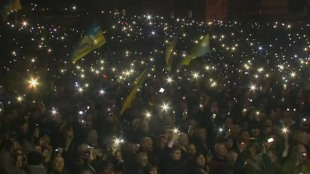 Ukrainian flags and lights shining from mobile phones