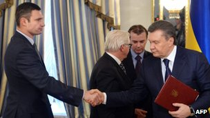 Head of Udar (Punch) party Vitali Klitschko (L) and Ukrainian President Viktor Yanukovych shake hands after signing an agreement in Kiev on 21 February 2014.