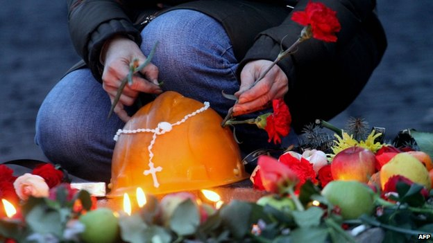 Woman places a flower on the helmet of a dead protester in Kiev (21 February 2014)
