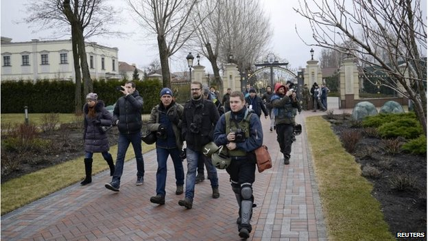 Journalists and protesters enter the presidential residential compound north of Kiev
