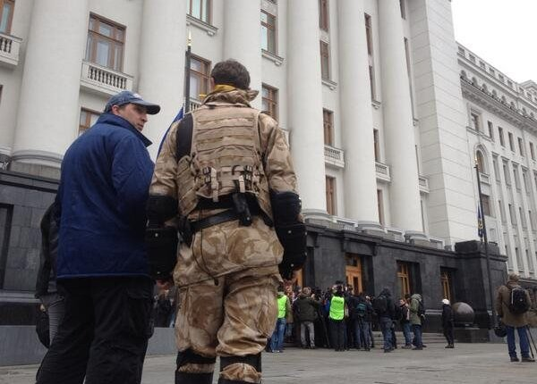 Protesters watch as reporters are shown around the grounds of the President's office in Kiev