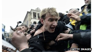 An alleged marksman in the pro-government forces is beaten by anti-government protestors in Kiev.