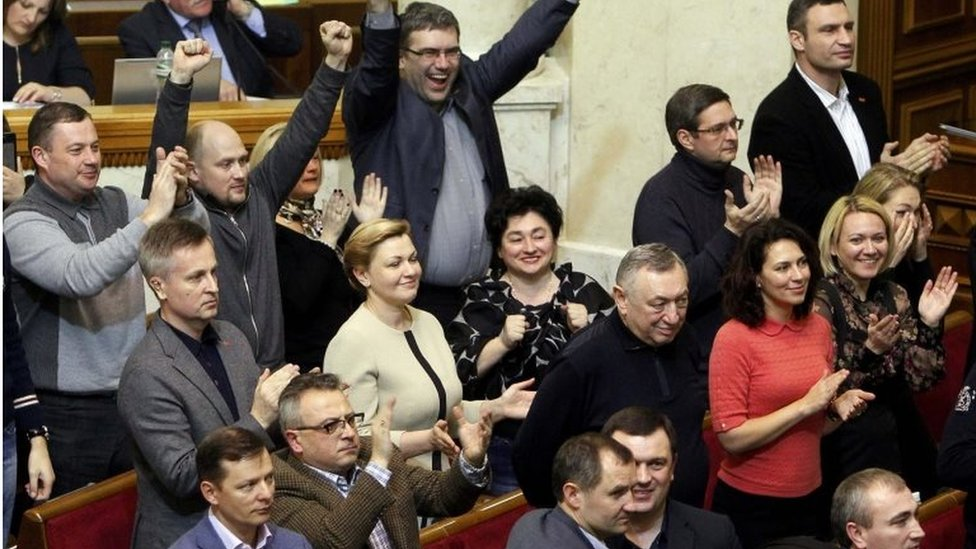 Parliamentarians celebrate after voting to oust Mr Yanukovych (22 Feb 2014)