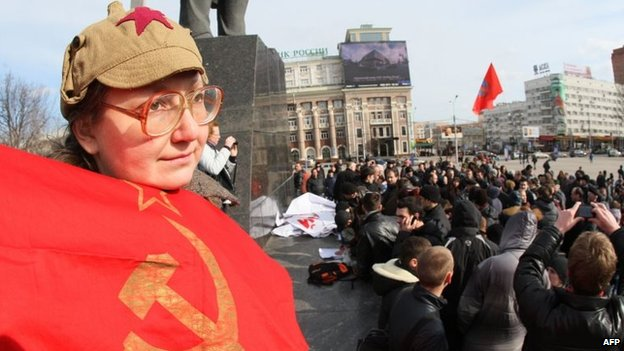A woman holds a USSR flag during a rally of a newly organized movement called Eastern Front in the eastern industrial city of Donetsk