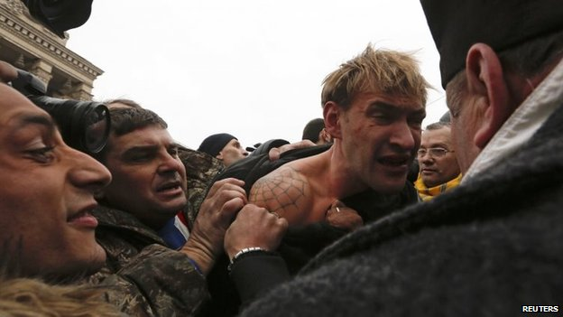 Anti-government protesters attack a man (C) whom they suspect of being a sniper