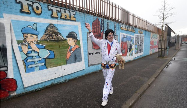 The Reverend Elvis, also known as Andy Kelso, waves from the peace line in west Belfast