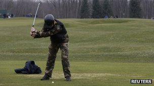 An anti-government activist plays golf