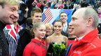 Russia's President Vladimir Putin (R) speaks with Evgeni Plushenko (L), Yulia Lipnitskaia (2nd L) and other Russian figure skaters after watching the Women's Figure Skating Team Free Program at the Iceberg Skating Palace during the Sochi Winter Olympics on February 9, 2014.