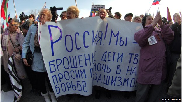 "Protesters in Sevastopol hold up a sign reading ""Russia, we have abandoned your children, we ask you to help in our fight against fascism"""