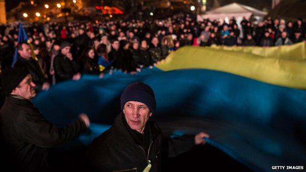 People hold a giant Ukrainian flag in Independence Square on 23 February 2014 in Kiev.