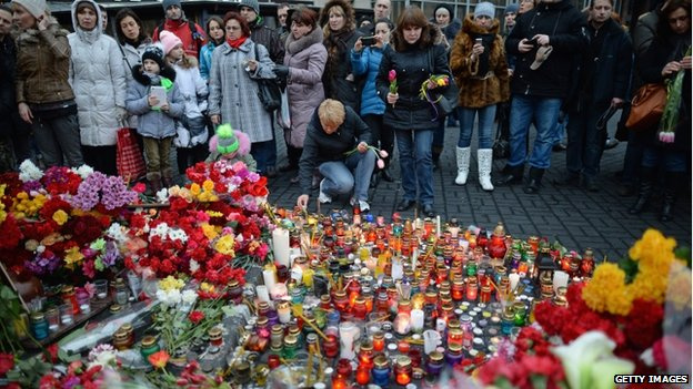 People view floral tributes to anti-government demonstrators killed in clashes with police in Independence Square on 23 February 2014 in Kiev.