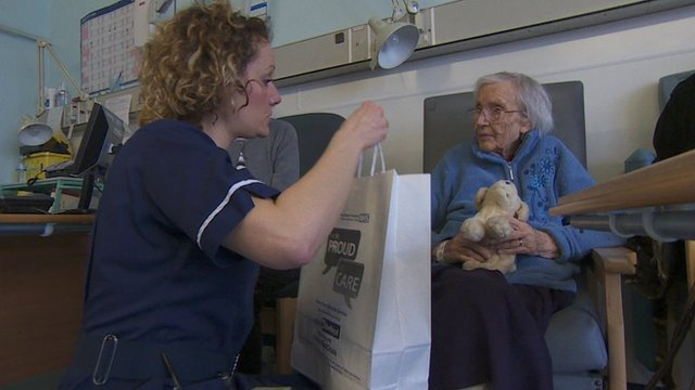 A nurse gives a food bag to an elderly patient