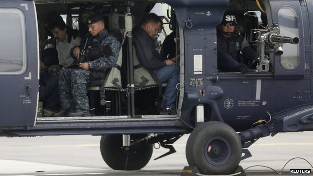 "Joaquin ""Shorty"" Guzman (in white shirt) in a Mexican federal police helicopter in Mexico City on 22 February, 2014."