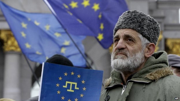 A Crimean Tatar protester in Kiev hold a flag with the Crimean Tatar symbol on an EU flag