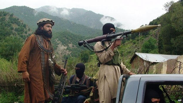 In this Aug. 5, 2012 file photo, Pakistani Taliban patrol in their stronghold of Shawal in Pakistani tribal region of South Waziristan.